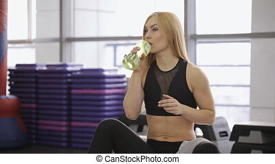 athlete sexy woman drinks water with a towel and rub the face and neck, with long hair in the gym