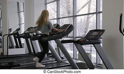 athlete sexy woman walking, with long hair walking on a treadmill in the gym in front of panoramic windows