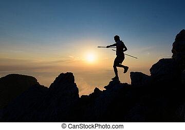 Athlete skyrunner in silhouette on the downhill rocks