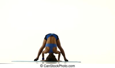 Athlete stands on his head and trains the body. White