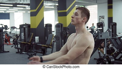 Athlete Stretches his Arms - A bare-chested athlete...