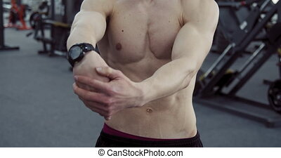 Athlete Stretches his Arms - Close up view of bare-chested...