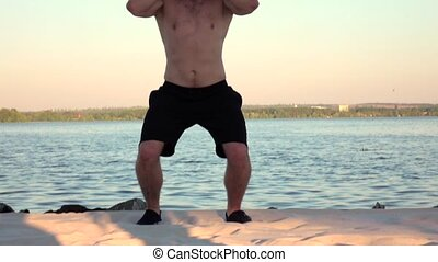 Athlete to raise two dumbbells over your head. Slow motion -...