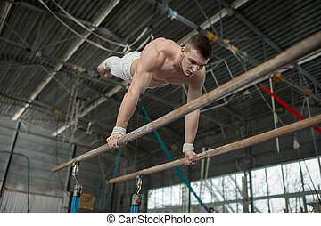Athlete topless doing exercises on the uneven bars in the gym.