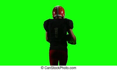 Athlete touches the ball in his hands and running. Green screen, back view,