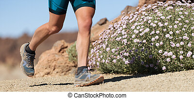 Athlete trail running in the mountains on rocky terrain