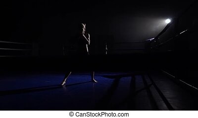 Athlete trains in the dark ring beats her legs . Silhouette....