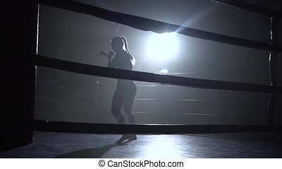 Athlete trains in the ring a dark space shines a spotlight -...