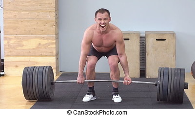 Athlete Trains With A Barbell In The Gym. Slow motion