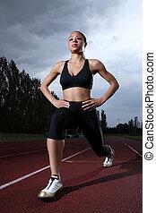 Athlete warm up stretch on athletics running track