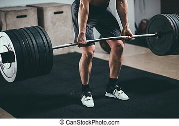 Athlete wearing black shorts lifting big barbell - Muscular...