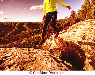 Athlete while jumping during a trail running in the mountains
