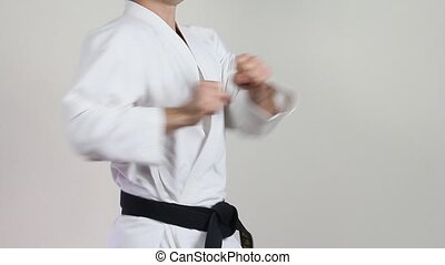 Athlete with a black belt on a light background makes the punch