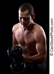 athlete with a dumbbell isolated on a black background