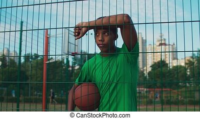 Thoughtful african american athlete holding basketball, leaning on sports fencing with hands on forehead, pondering about something while standing on outdoor urban court in early morning.