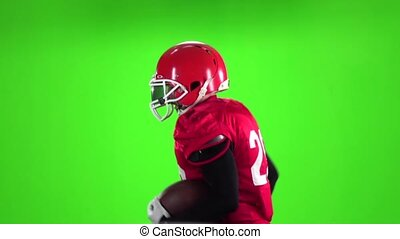 Athlete with the ball and in a helmet runs. Slow motion. Green screen