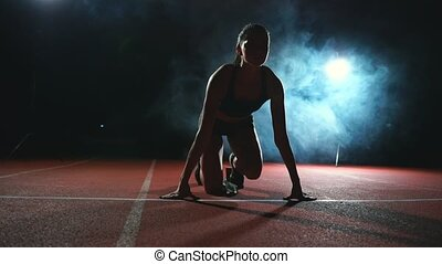 Athlete woman in black shorts and a t-shirt in sneakers are...
