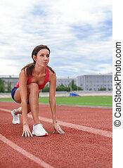 Athlete woman on the starting blocks