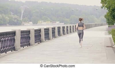 Athlete woman running on city embankment while outdoor...