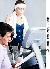 Athlete woman training on gym equipment in gym with coach
