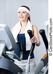 Athlete woman training on gym equipment in gym