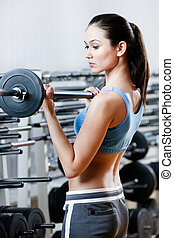 Athlete woman with dumbbells in sport centre