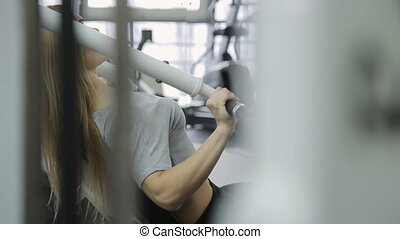athlete woman with muscular body doing exercise on the chest and biceps straining their muscles in the gym.