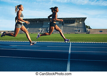 Athletes arrives at finish line on racetrack during training...