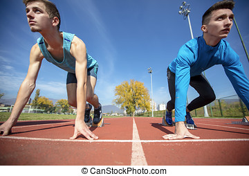 Athletes at the sprint start line in track and field