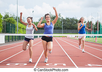 Athletes celebrating as they cross finish line