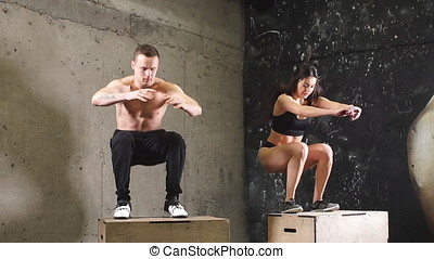 Athletes doing box squat exercise in CrossFit gym, Slow...