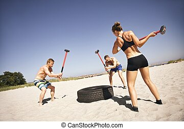 Athletes doing crossfit workout on beach - Three strong ...