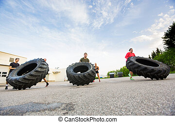 Athletes Doing Tire-Flip Exercise - Group of young athletes...