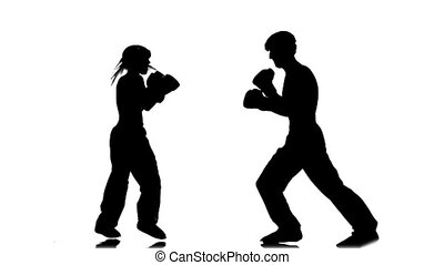 Athletes in sparring practice the correct blows. Silhouette....