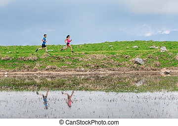 Athletes in training in the mountains are reflected in the lake as they run
