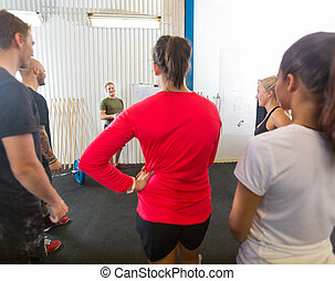 Athletes Listening To Instructor At Gym
