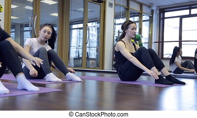 Athletes lying on the floor lift the body to the knees in the gym.