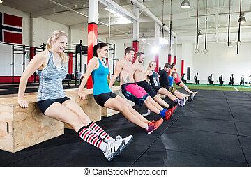 Athletes Performing Triceps Dips In Gym