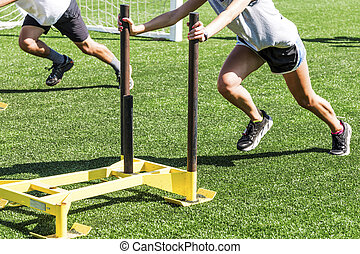 Athletes pushing weighted sleds on a turf field - Two cross...