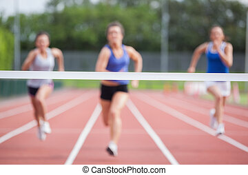 Athletes racing towards finish line - Female athletes racing...