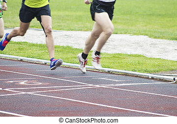 athletes running on the athletics track