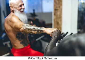 Athletes with different age and race doing bike exercises in gym - Fit people training on cycling machine in health wellness center - Sport activity and fitness lifestyle concept