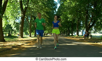 Athletic attractive couple running in public park