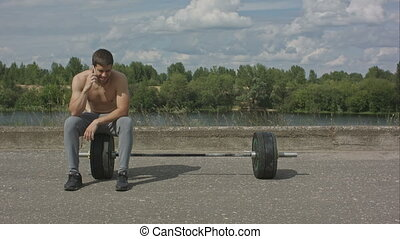 Athletic bearded man with muscular body having phone call after training outdoor