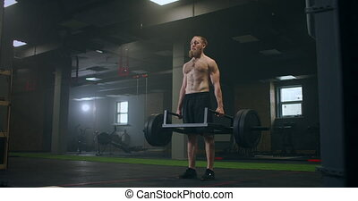 Athletic Beautiful man Does Deadlift with a Barbell in the Gym. Gorgeous male Professional Bodybuilder Workout Weight Lift Exercises in the Authentic Fit Training Facility. High quality 4k footage
