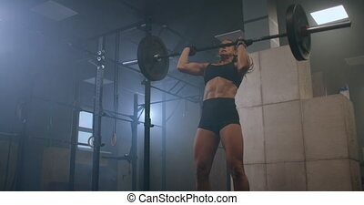 Athletic Beautiful Woman Does Overhead Deadlift with a Slow motion: Barbell in the Gym. Gorgeous Female Professional Bodybuilder Workout Weight Lift Exercises in the Authentic Fit Training Facility. High quality 4k footage