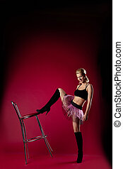 young woman in dance sport costume kick chair