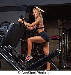 Athletic blonde woman in sportswear posing near the legs press machine in a gym.