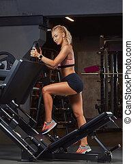 Athletic blonde woman in sportswear posing near the legs press machine in the gym.