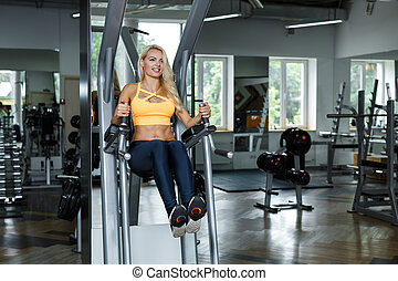 Athletic blonde woman  using press machine  in gym